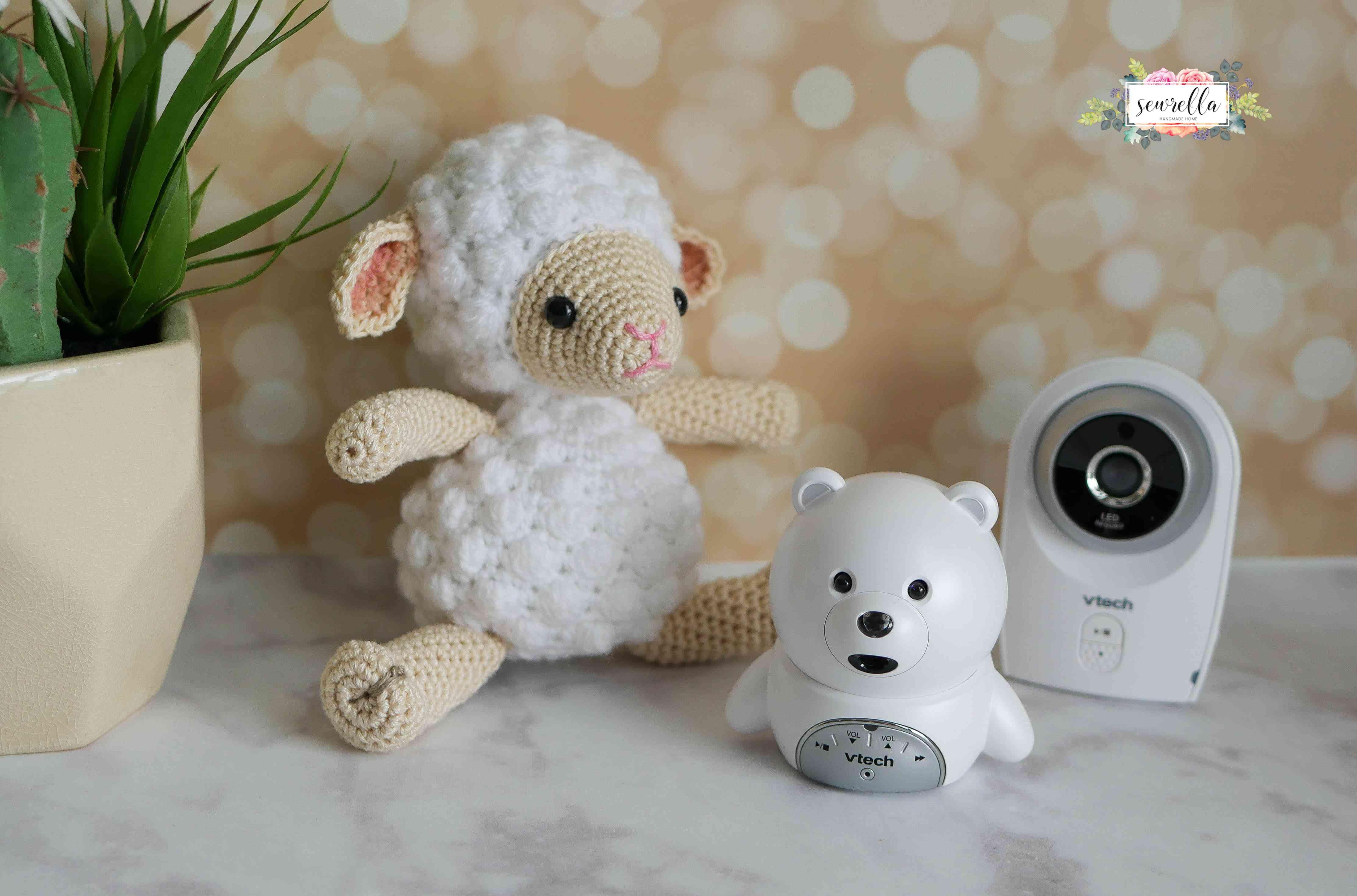 Small white crochet lamb next to baby monitors.