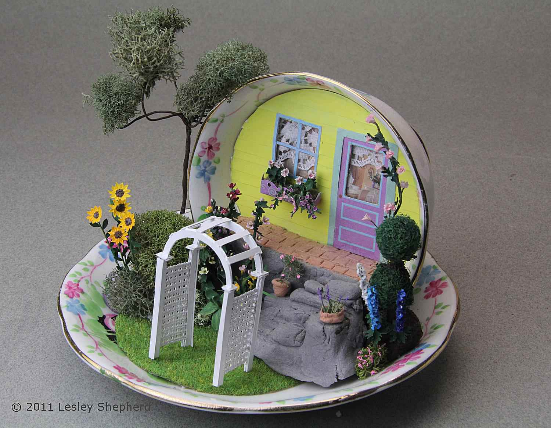 Quarter scale garden arbor set in a miniature garden scene in a tea cup.
