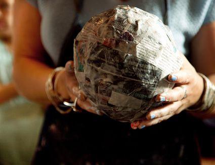 Woman holding completed papier-mâché project