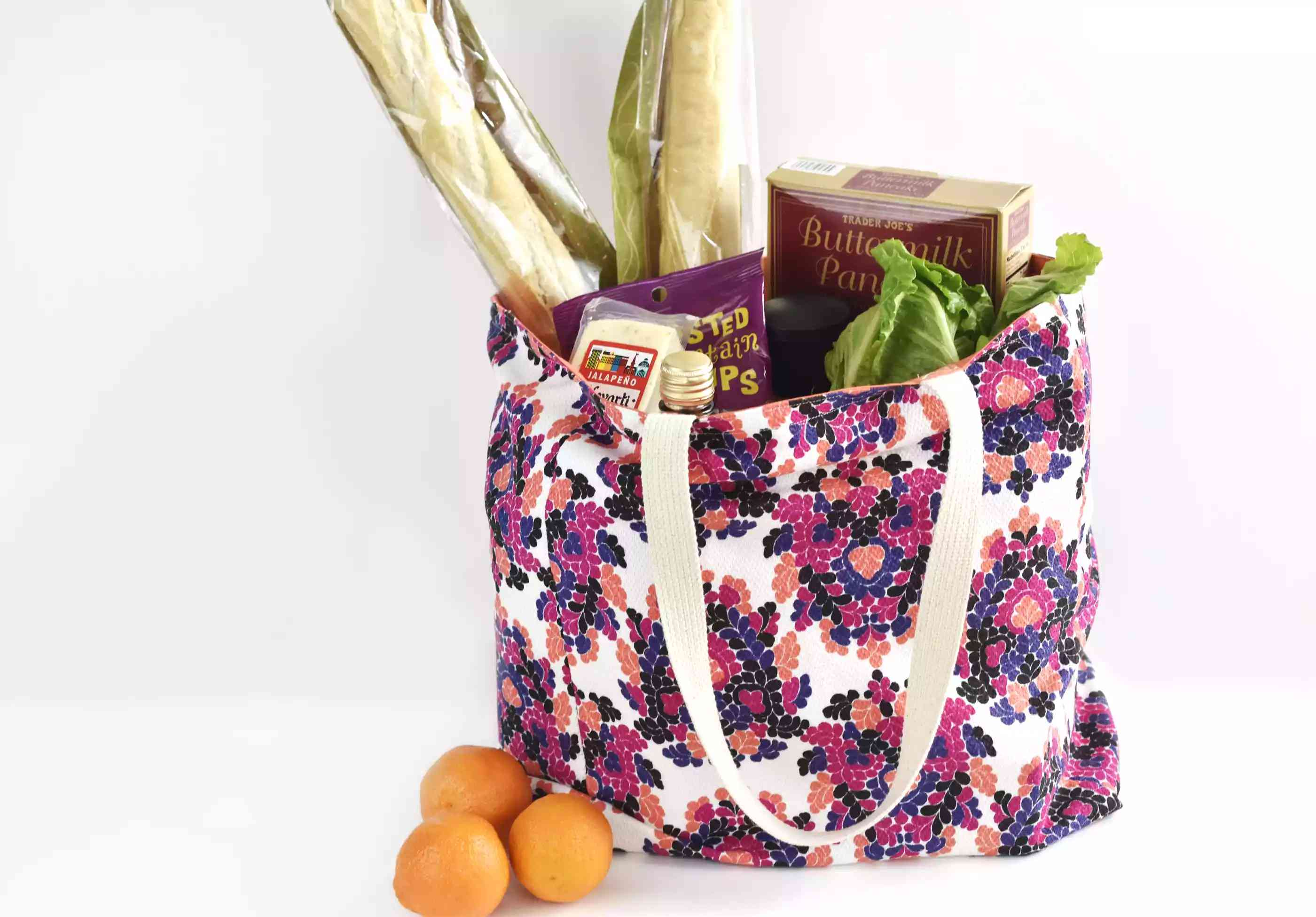 A purple floral reusable grocery bag filled with groceries