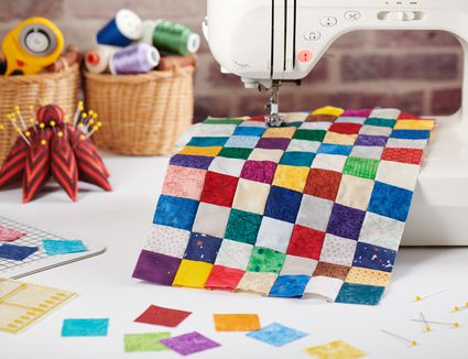 Colorful detail of quilt sewn from square pieces on sewing machine, quilting and sewing accessories