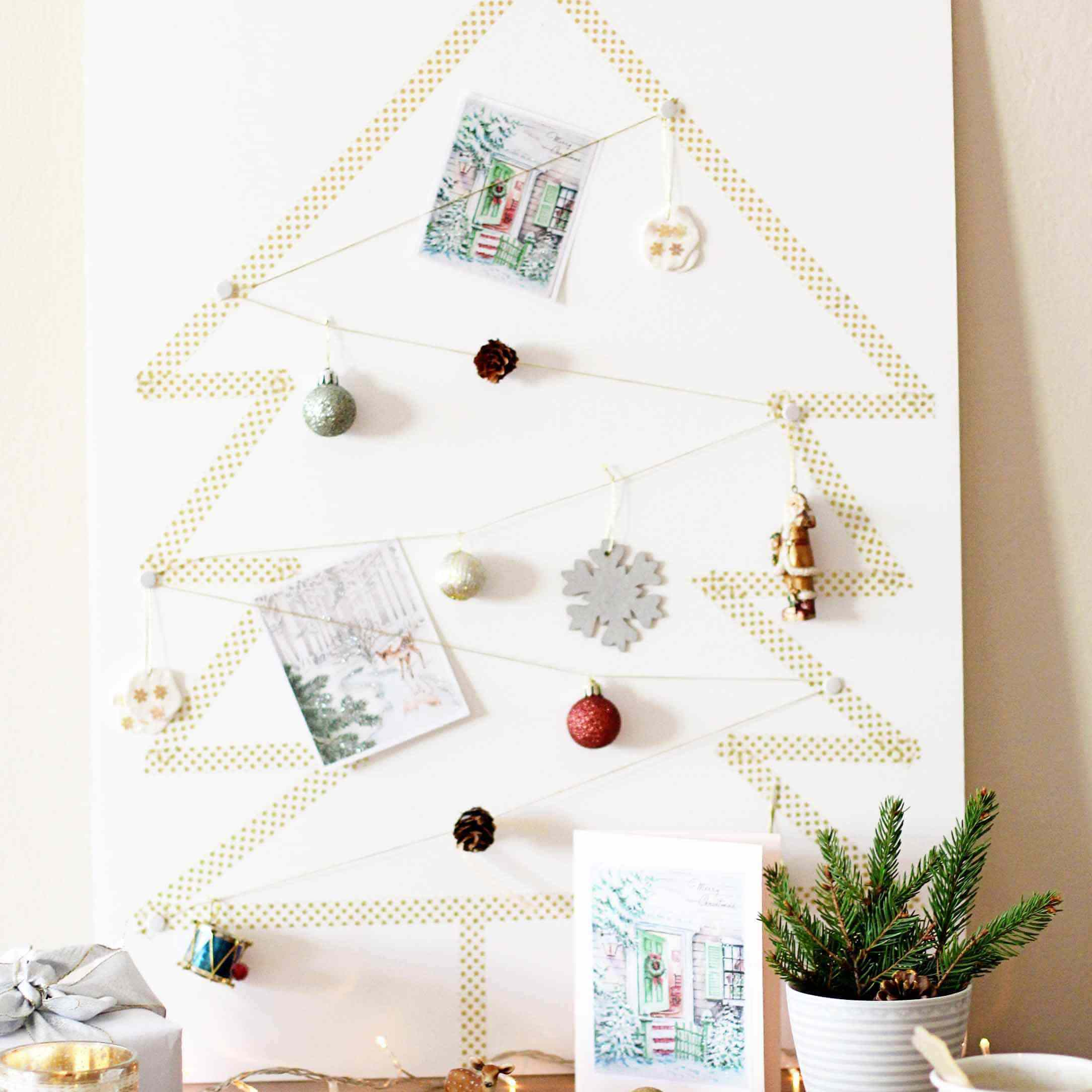Washi tape in the shape of a tree on a canvas with small ornaments and photos.