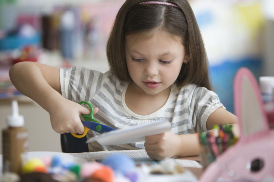 Caucasian Girl Cutting Paper With Scissors