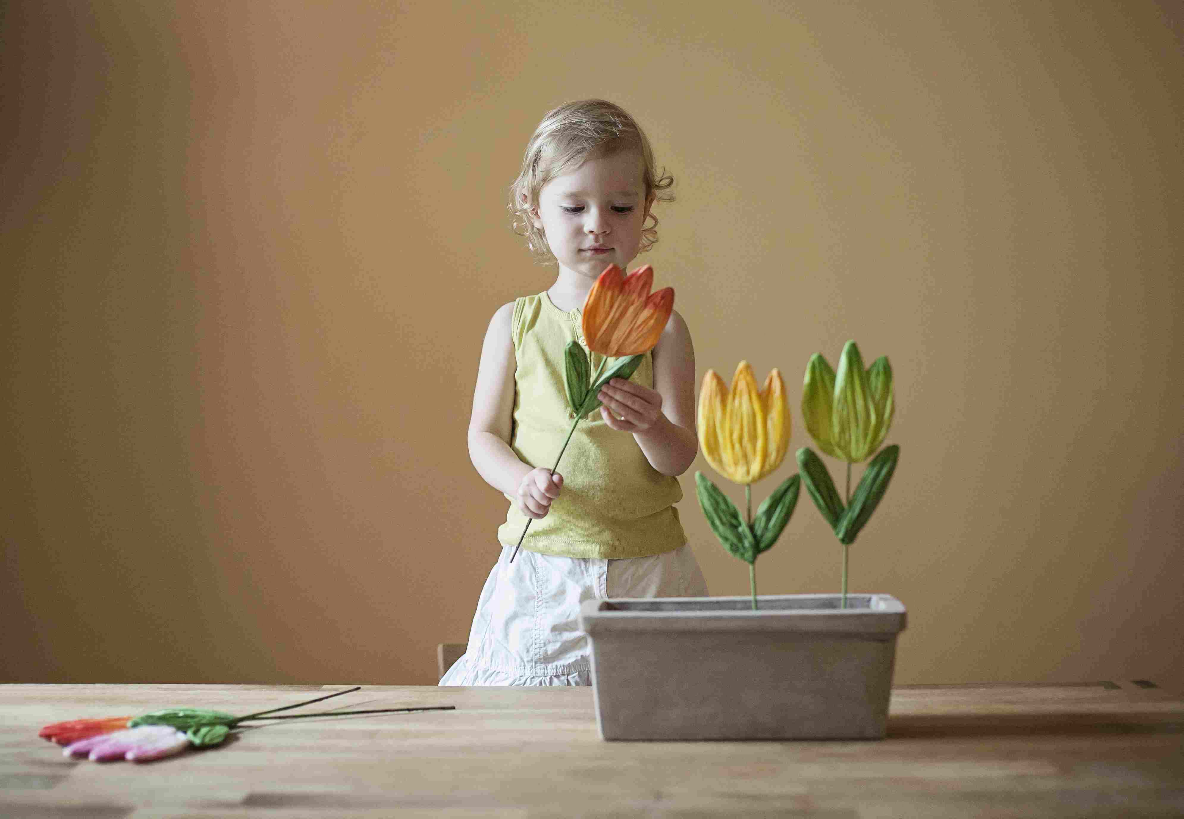 girl playing with paper flowers