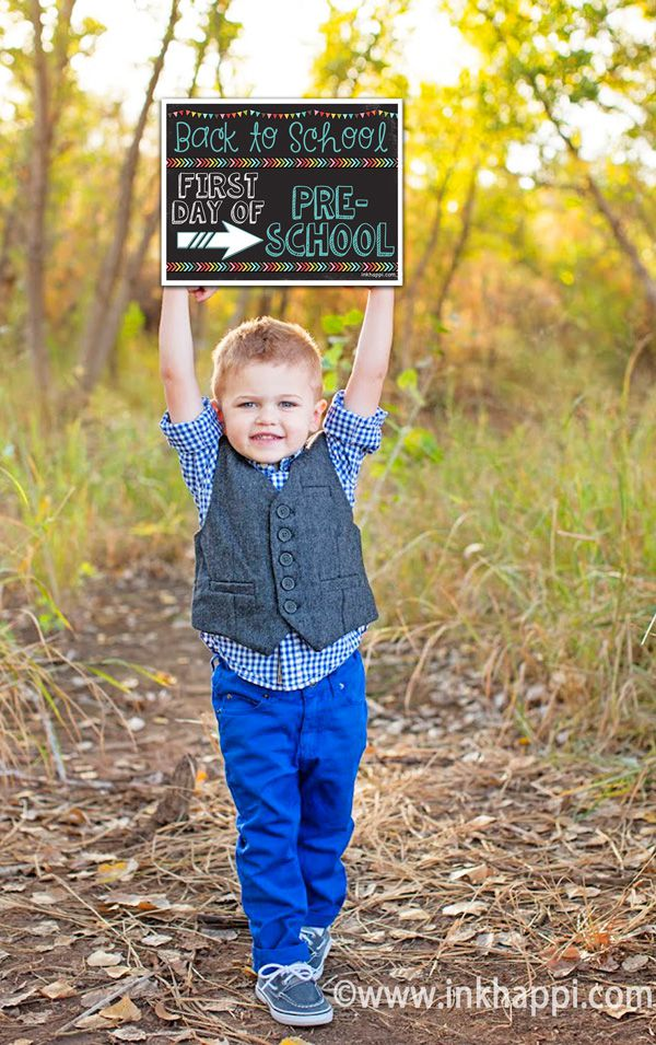 A young boy holding a first day of preschool sign.