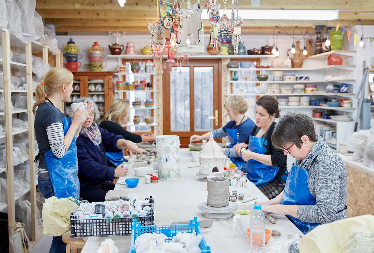 A group of people seated at a workbench in a pottery workshop.