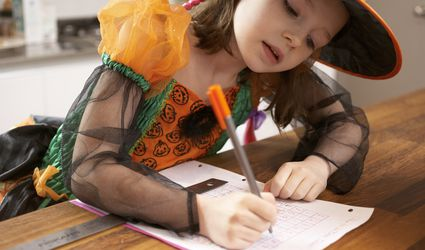 Child studying in Halloween costume