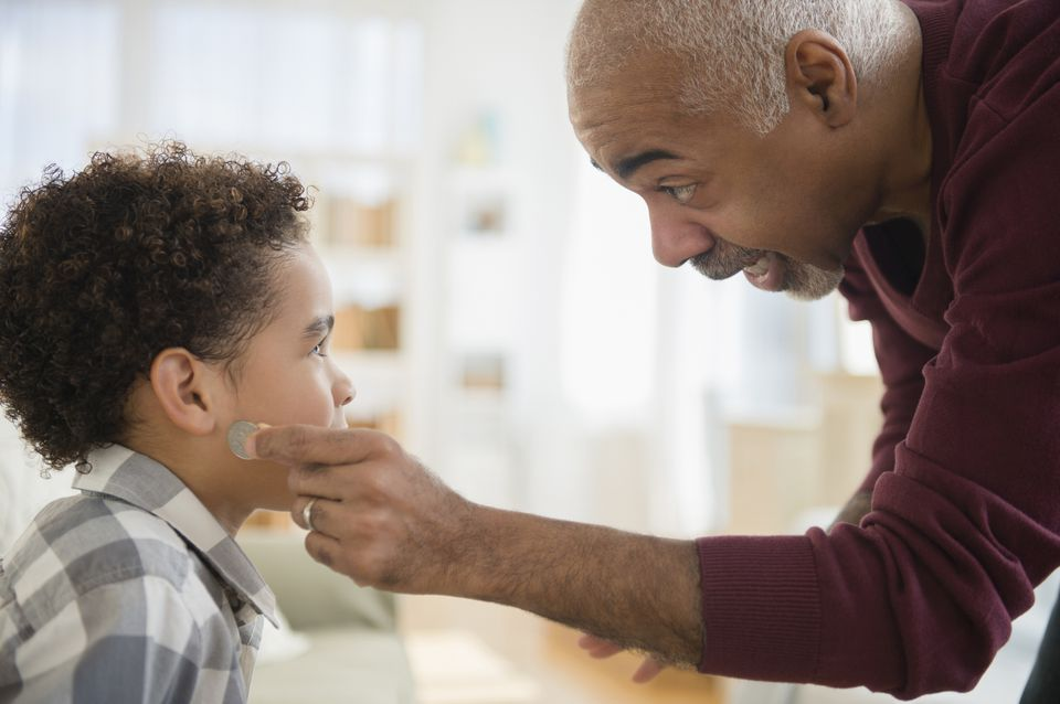 Grandfather pulling magic coin from grandson's ear