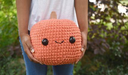 A Teen Holding a Giant Happy Crocheted Pumpkin