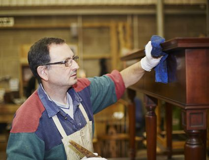 Craftsman applying wax finish to furniture