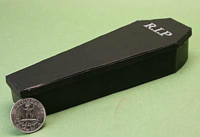 miniature paper coffin box next to a quarter to show scale