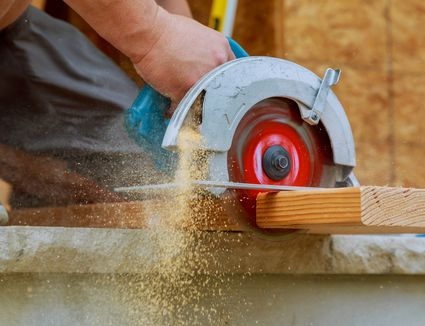 Worm drive saw cutting through 2x8 on construction site