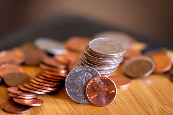 Stacks of coins with quarter and penny in front