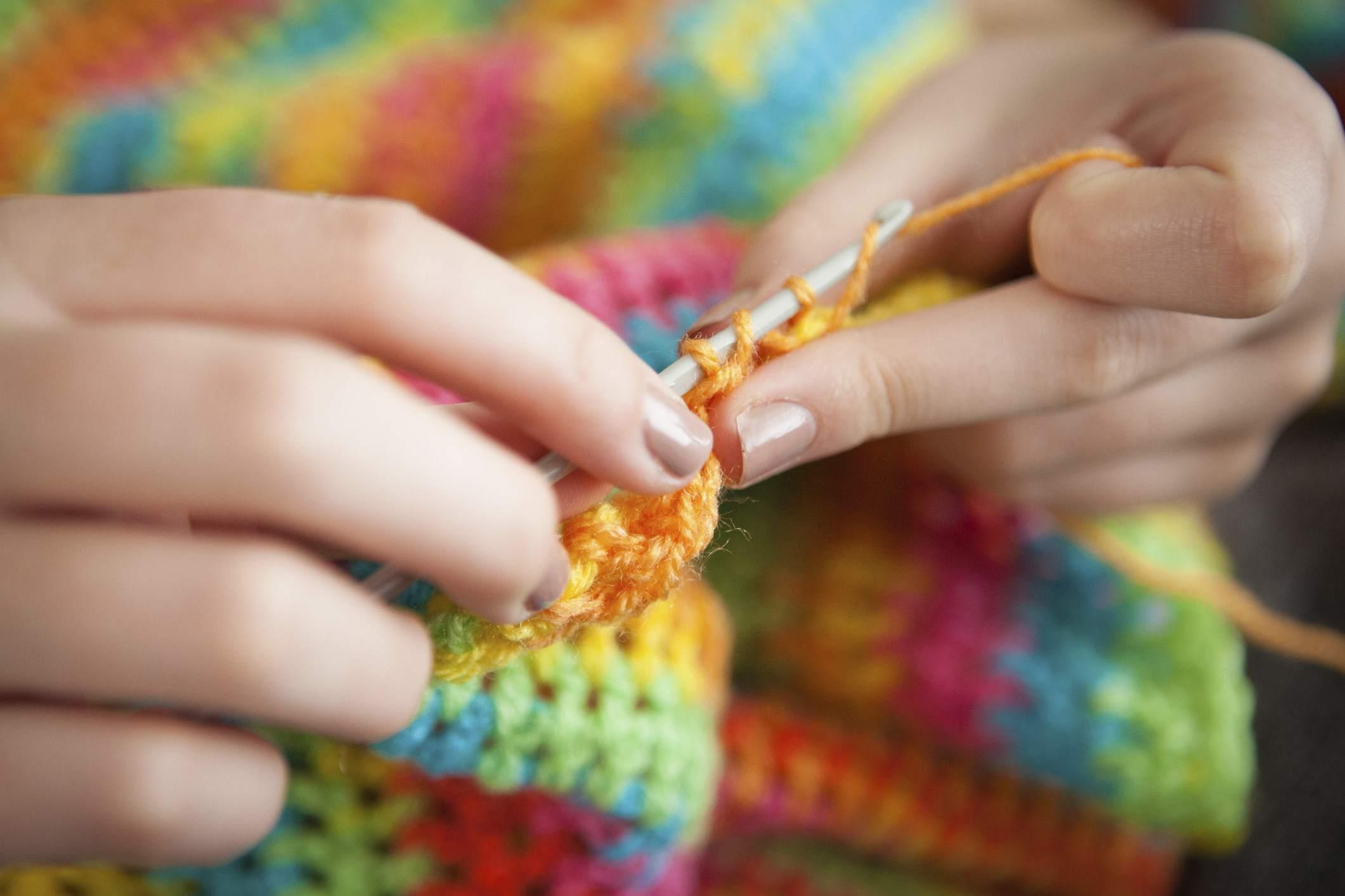 Women crocheting a rainbow blanket