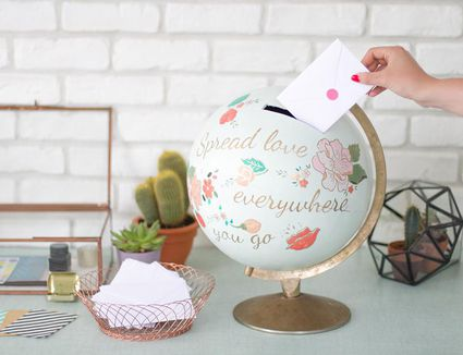 Someone placing a card in a DIY card box made from a painted globe.