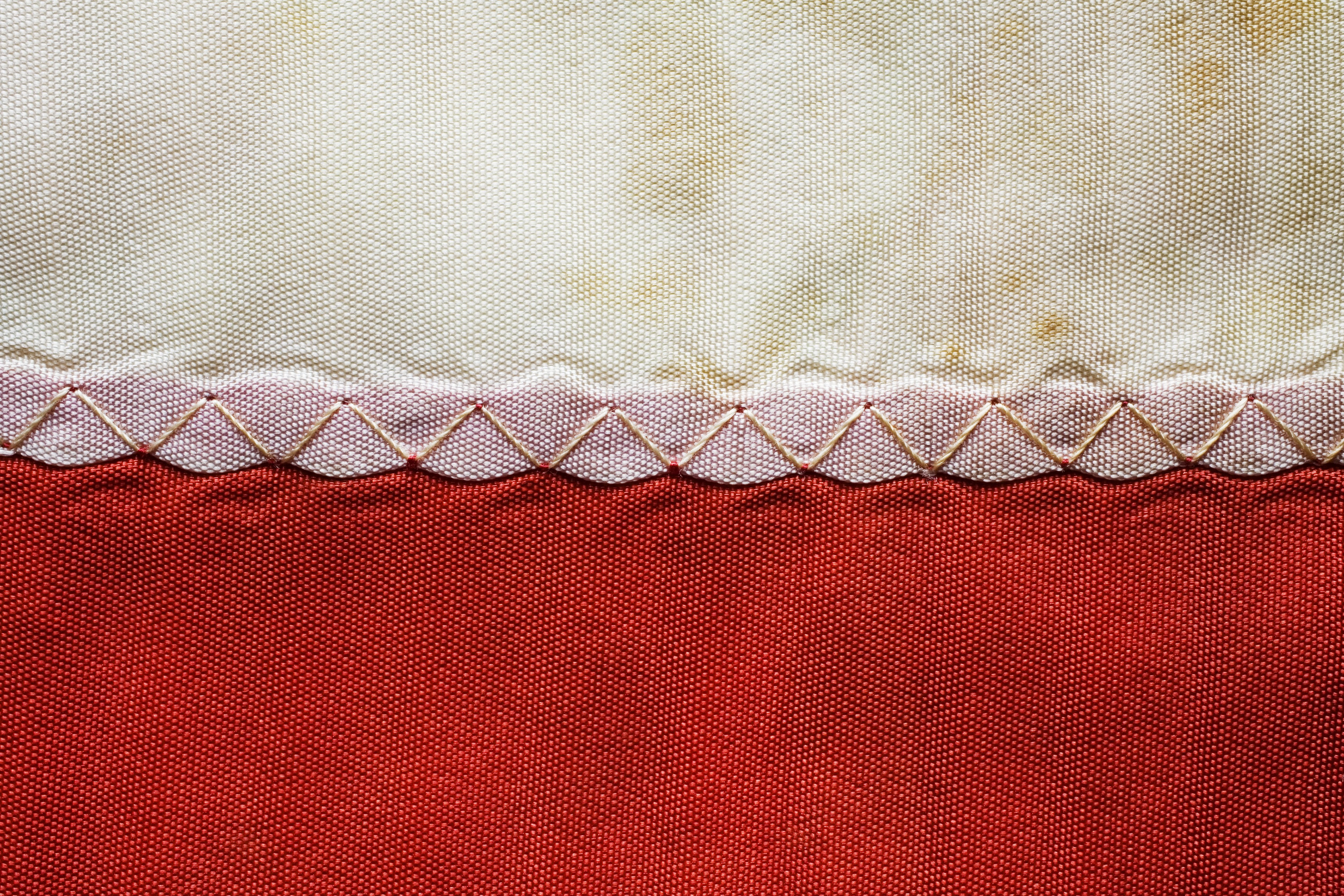 Decorative zig-zag stitch on heavy cotton fabric of an old flag, close-up