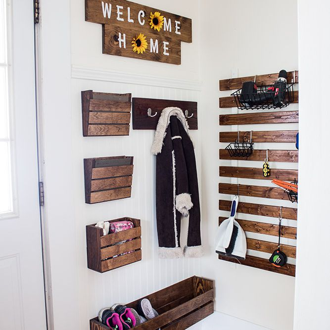"""Scrap wood wall organizer hanging on a white wall under a """"welcome home"""" sign"""