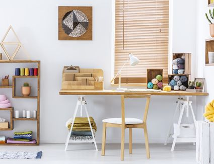 Real photo of a creative room interior with a desk, threads, knitting wool and graphic on a wall
