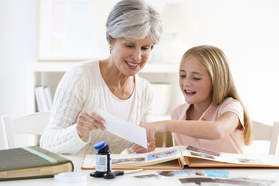 Grandmother and granddaughter (9-11) working on scrap book at home