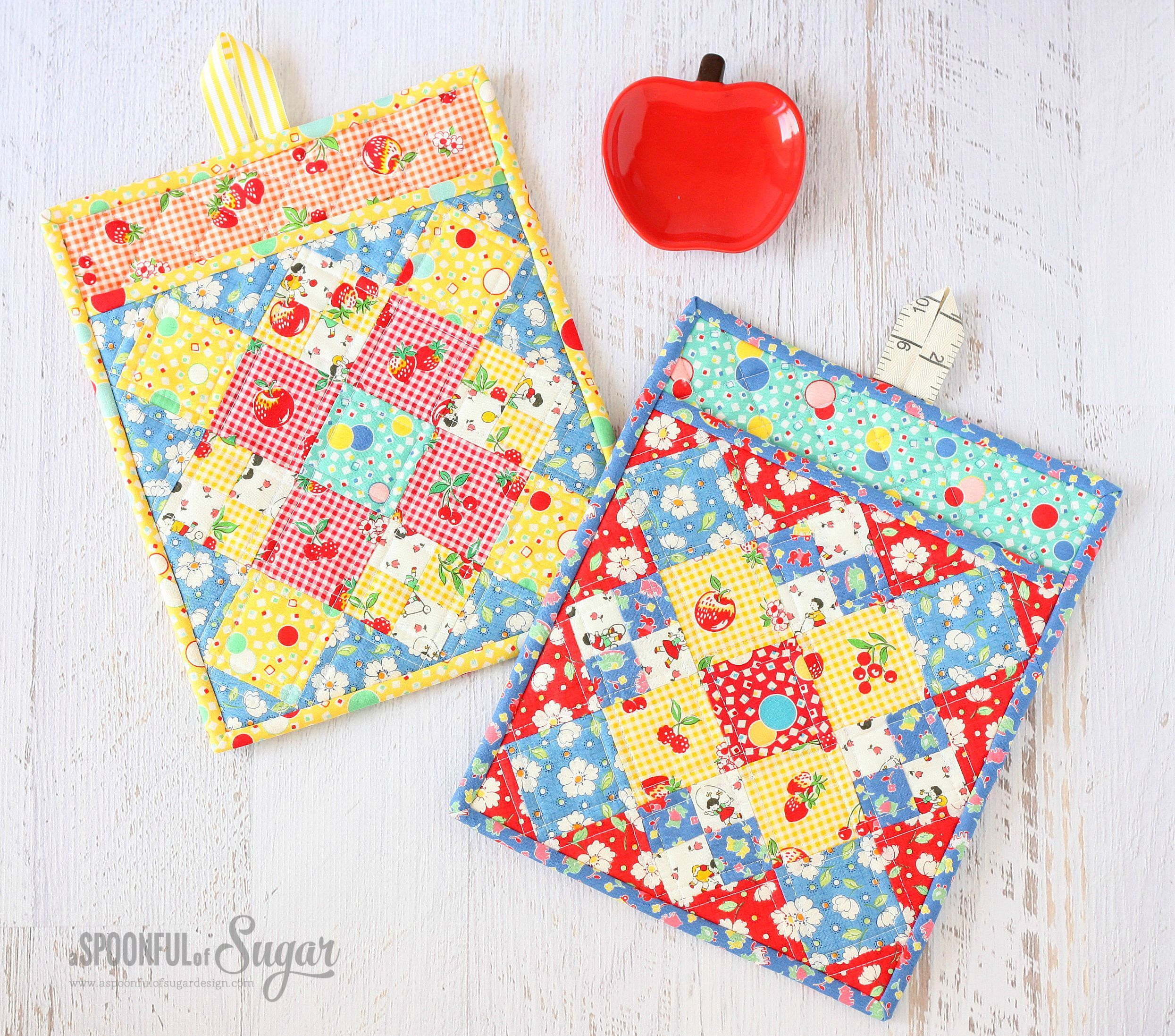Two patchwork pot holders on a table