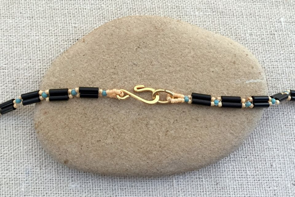 Close up of necklace clasp on a stone.