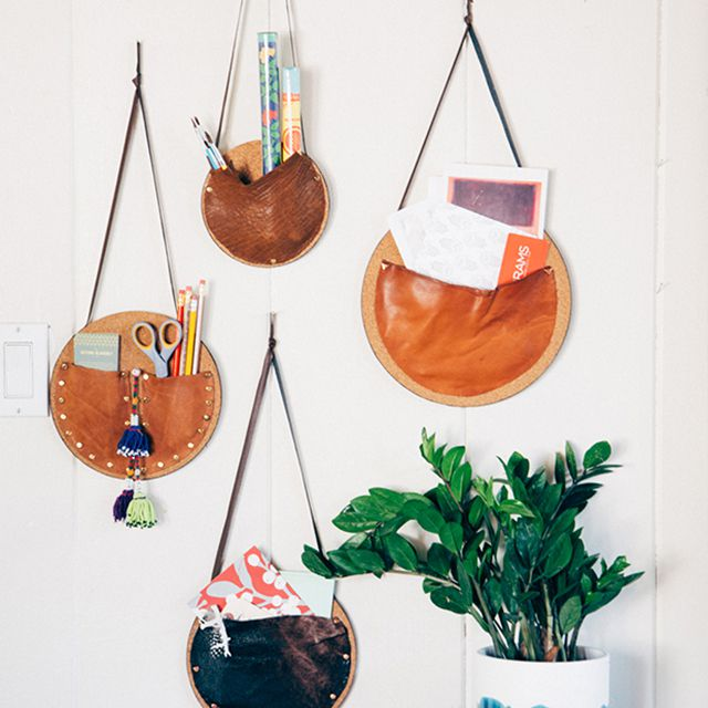 wall pocket organizers hanging on a wall above a plant made of leather and cork board