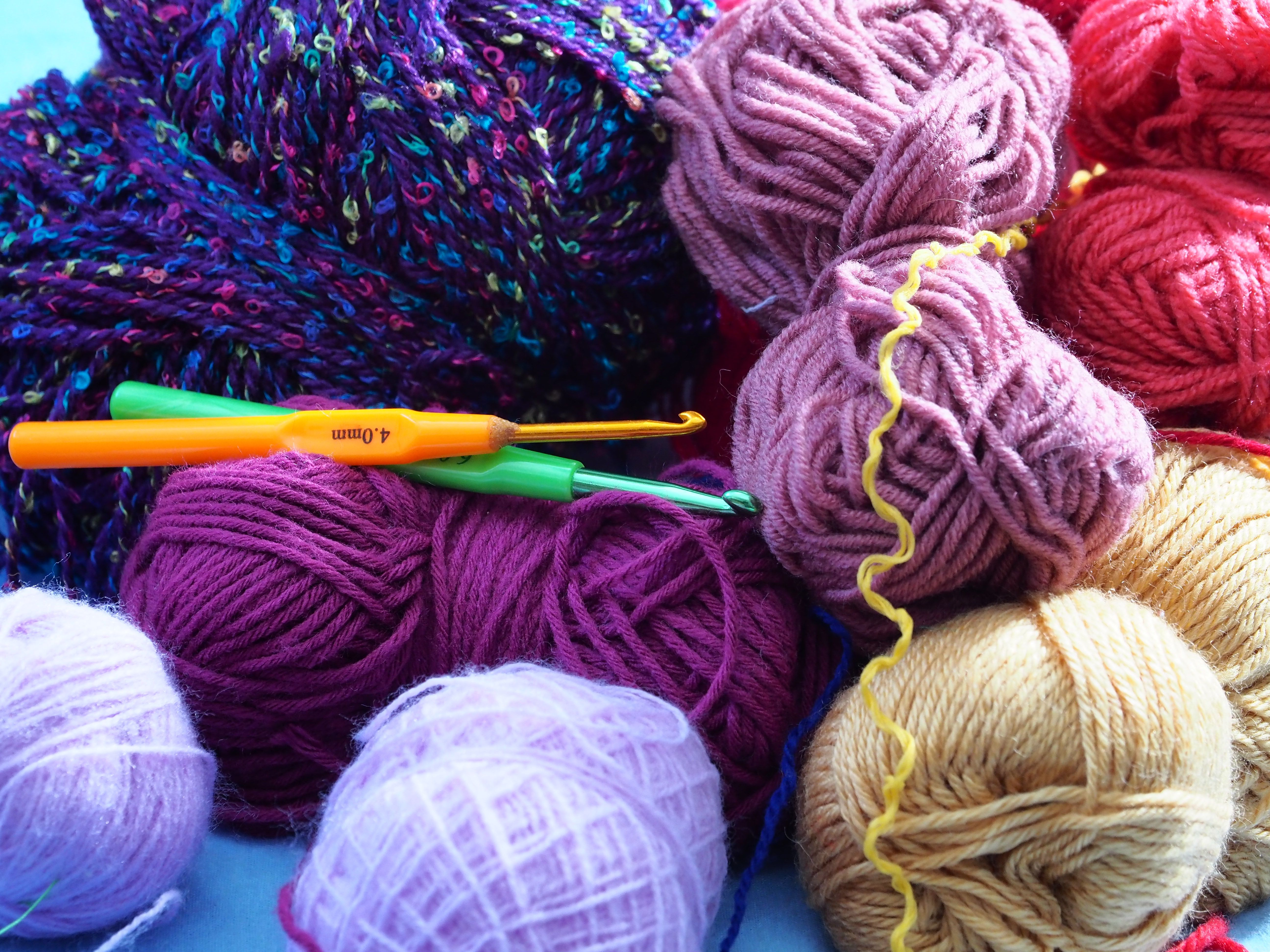 Knitting equipment, such as hooks and yarn, on a table.