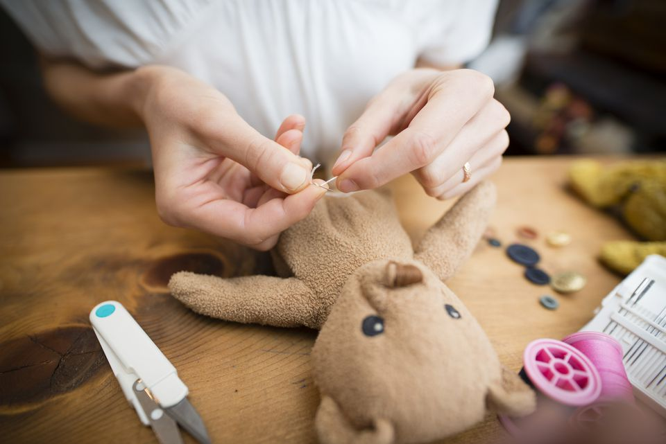 Woman threading needle to fix stuffed bear