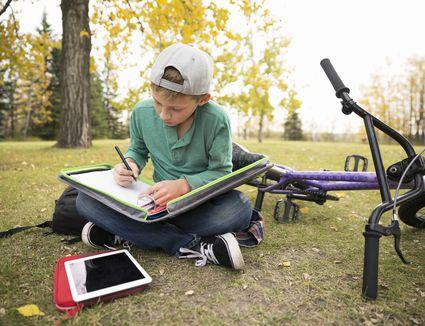 Tween boy doing homework in autumn park