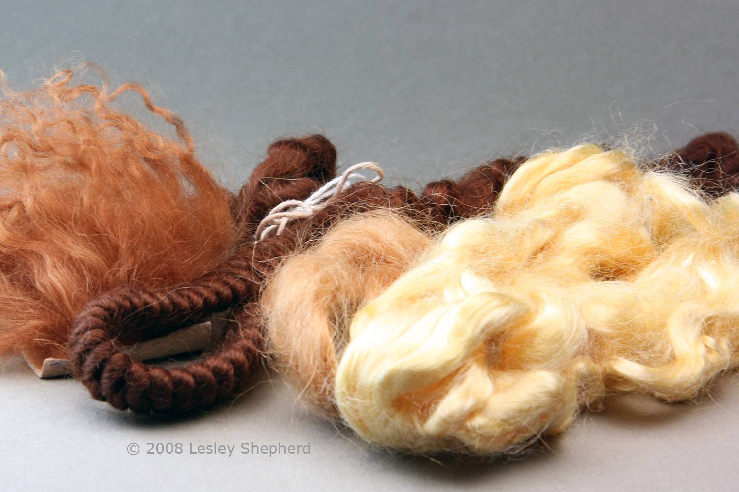 Some fibers used for making wigs for miniature dolls. These include (left to right) Tibetan lambs wool, braided and stranded mohair, and viscose.