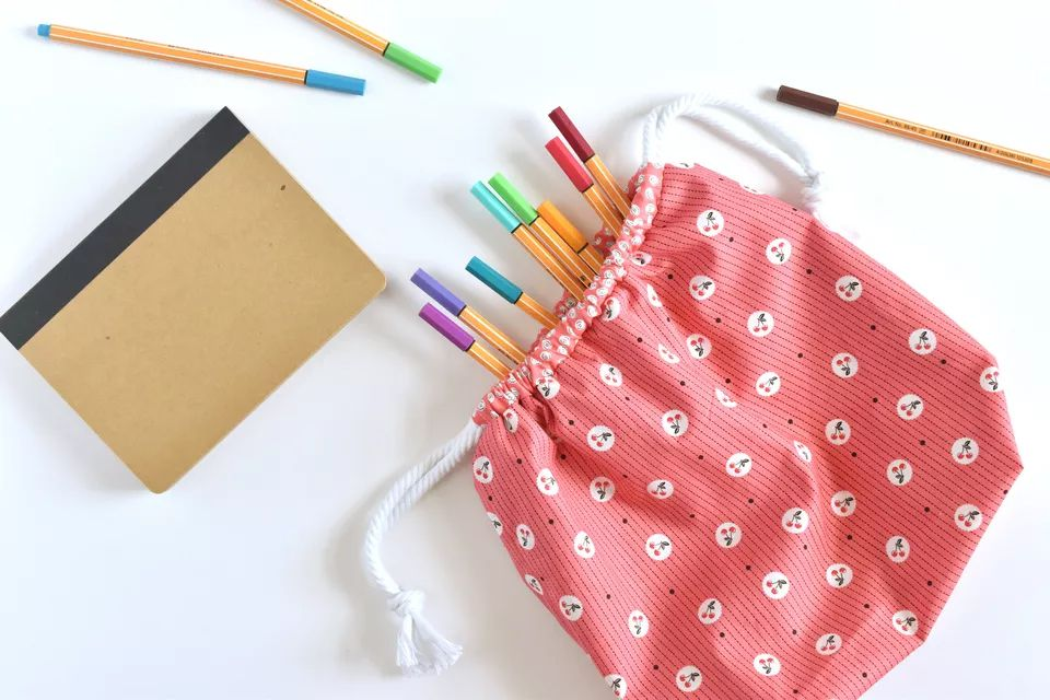 A pink floral drawstring bag with pencils and a notebook