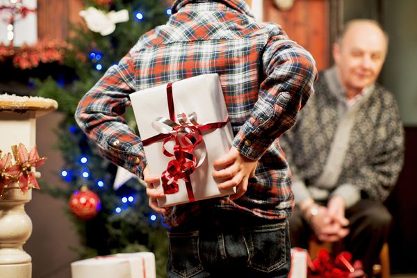 boy hiding gift behind his back next to a Christmas tree and old man