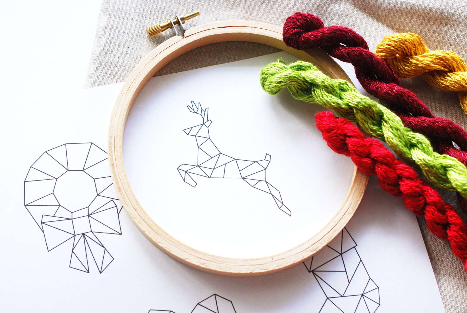 Geometric reindeer image on paper inside a hoop with thread to the side.