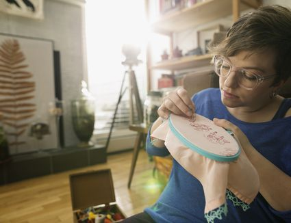 Woman with glasses cross stitching embroidering fabric