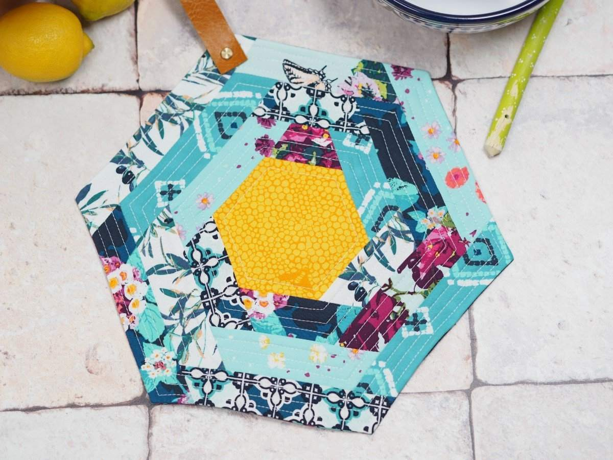 A colorful hexagon shaped pot holder with a leather strap