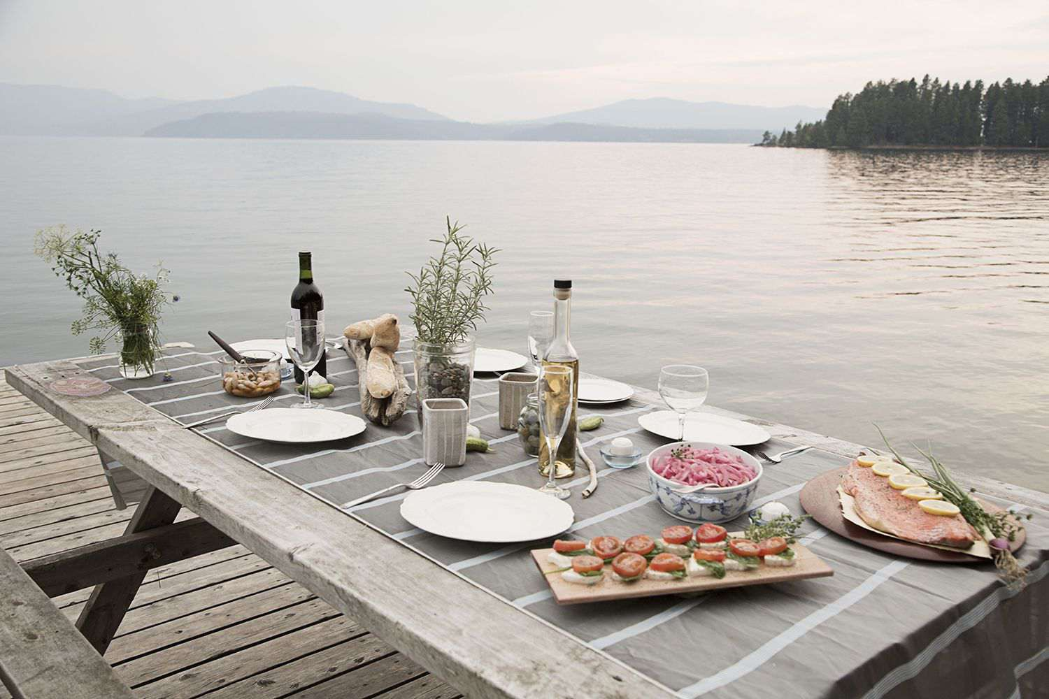 Plates of Food on Picnic Table Near Lake