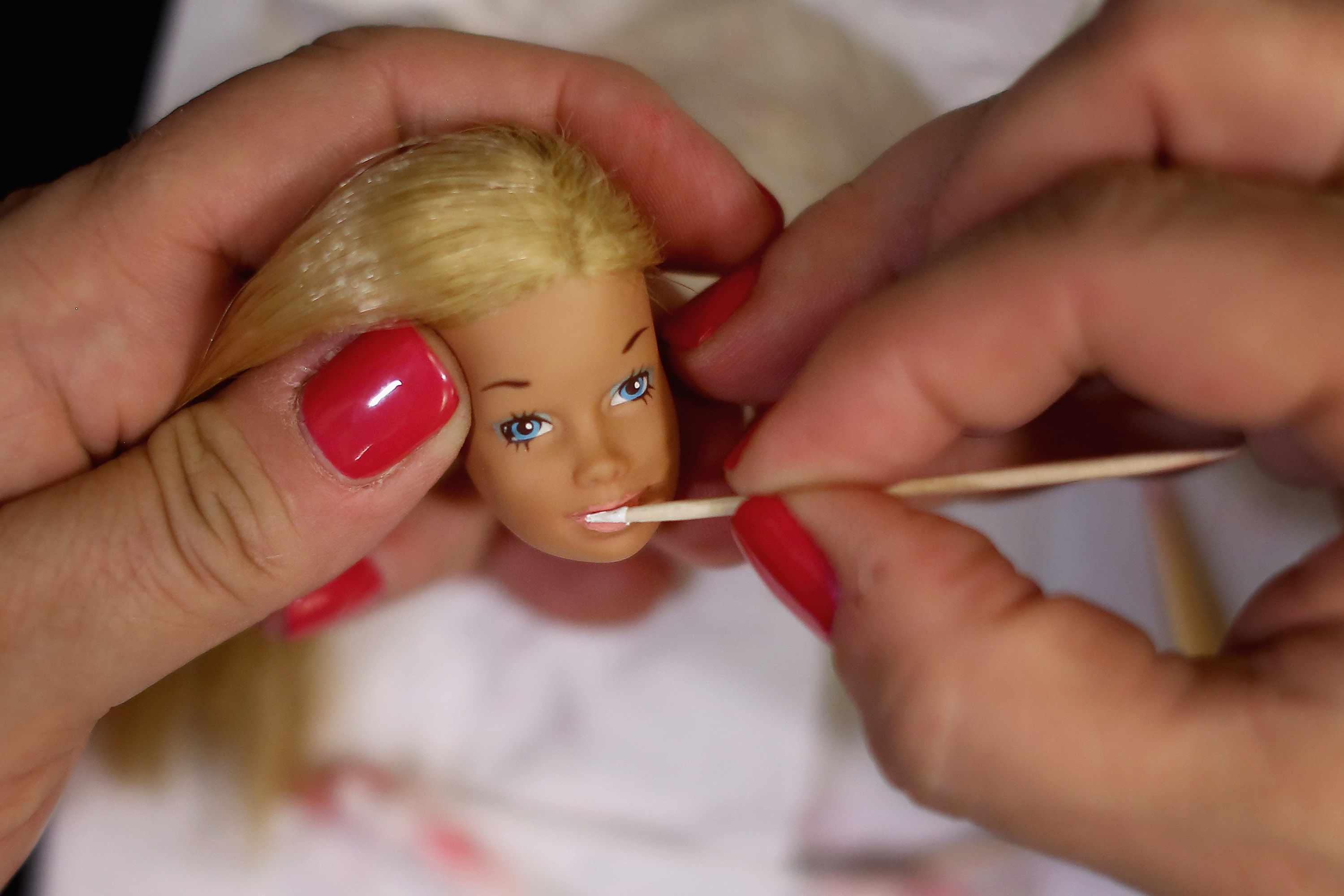 Someone painting new features on Barbie doll head