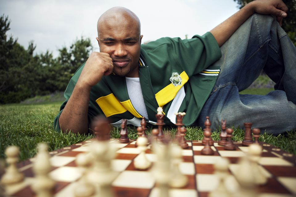 Man on grass pondering chess move