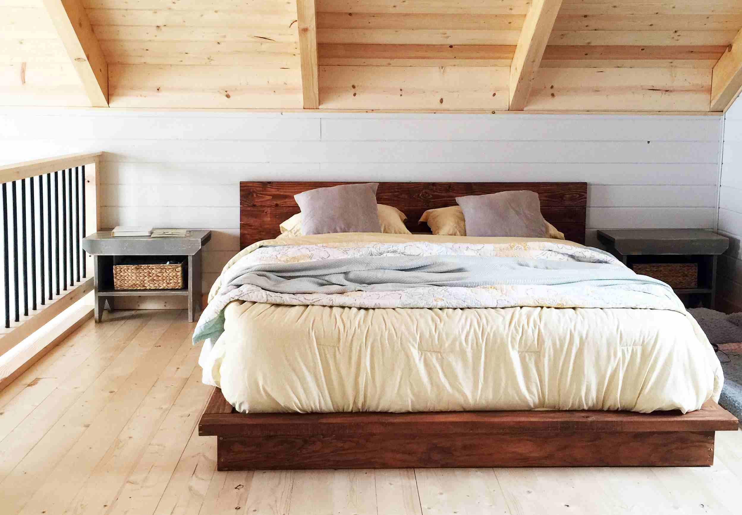 A king-sized platform bed in a loft