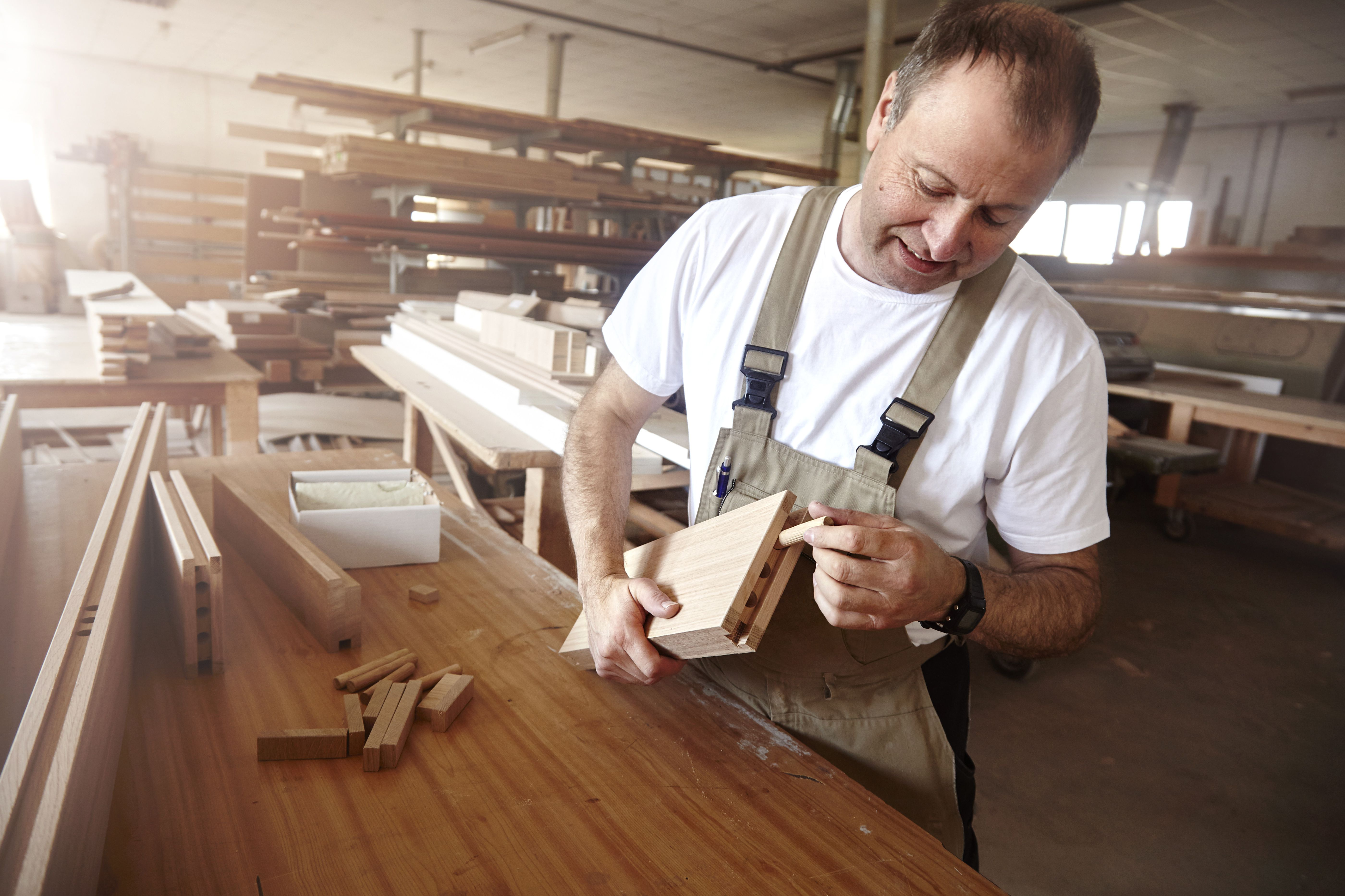 Male carpenter inserting wooden dowel at workbench