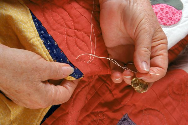Stitching a quilt by hand using specialized knots