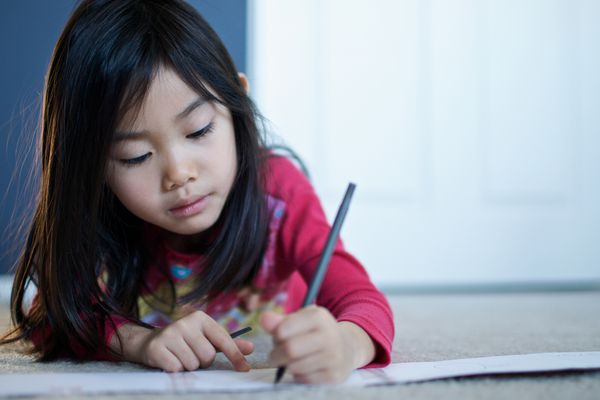 Young girl writing a letter on the floor