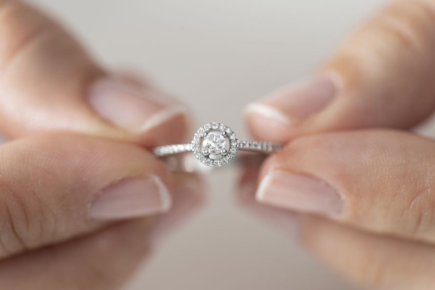 a woman's hands holding a diamond ring