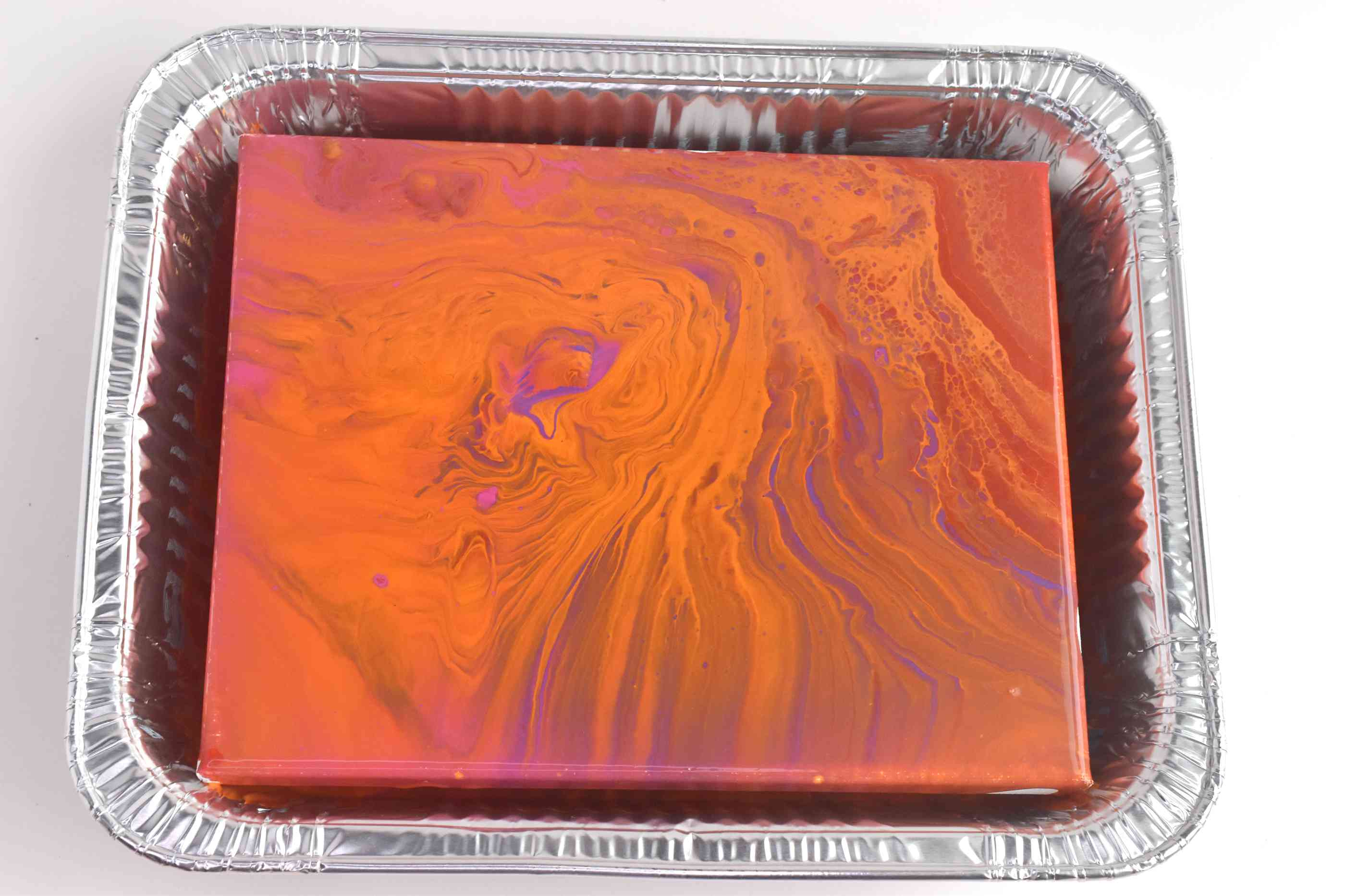 Pour painted canvas with swirls of orange, pink, bronze, and purple