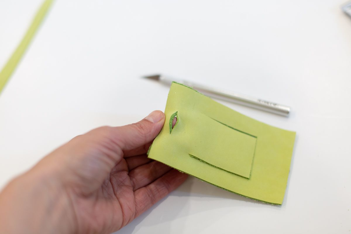 DIY leather luggage tag with a woman's hand showing a slit cut into the top of the tag