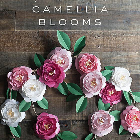 Paper Camellia flowers laying on a wooden table.