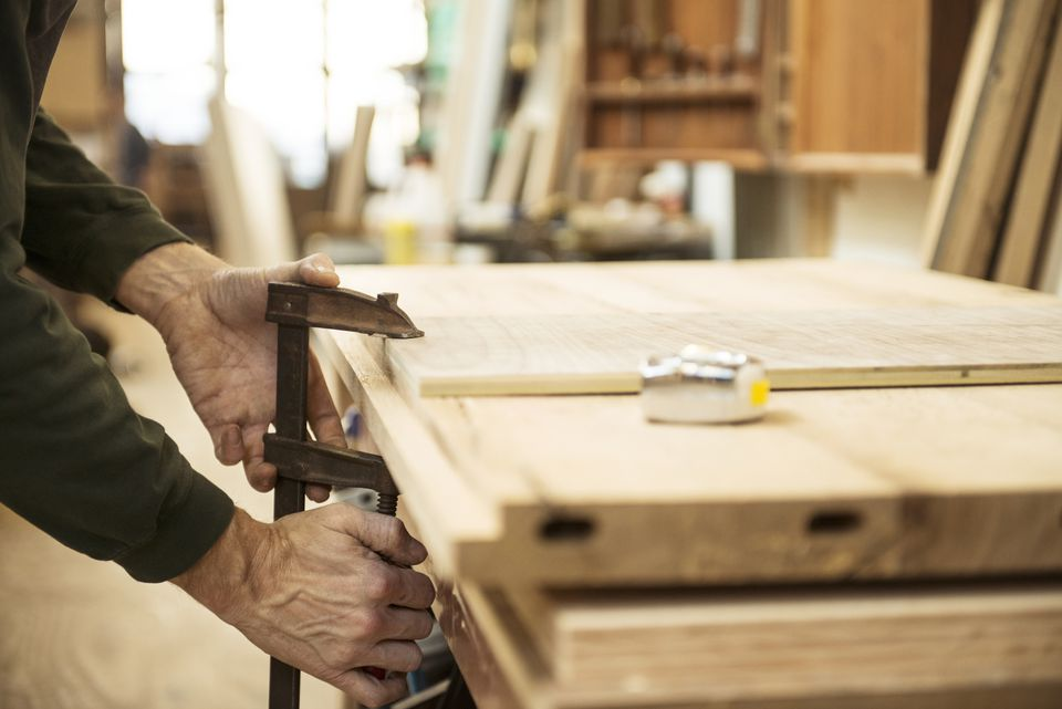 Man clamping wood to a table