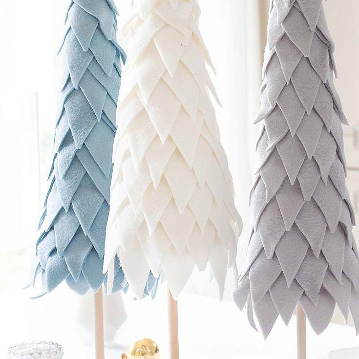 Textured white, blue, and grey Christmas trees made from pieces of felt.
