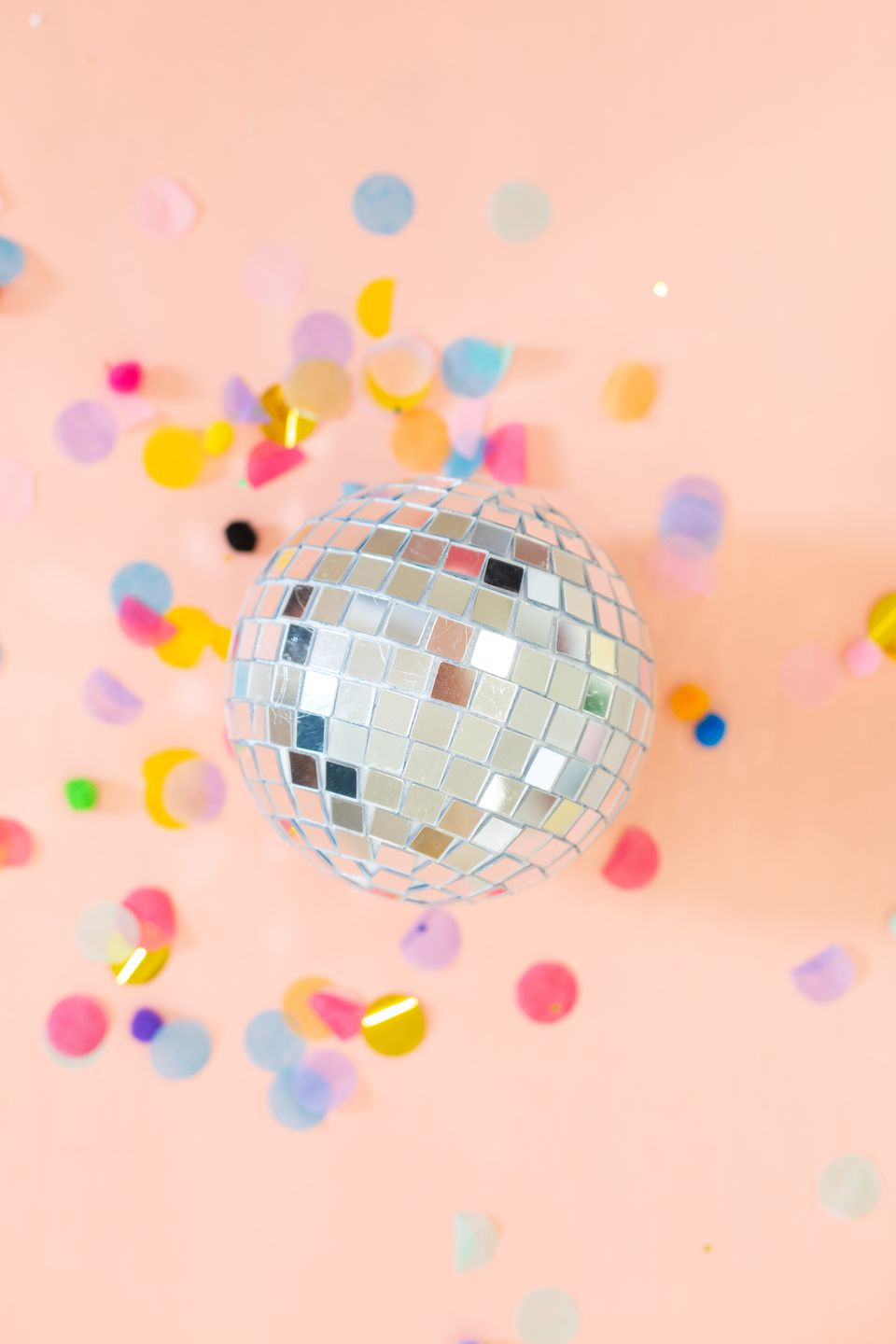 DIY disco ball on pink background with confetti