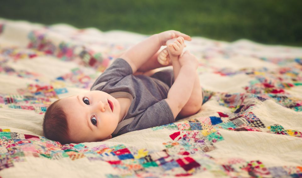 Baby boy lying on vintage quilt.